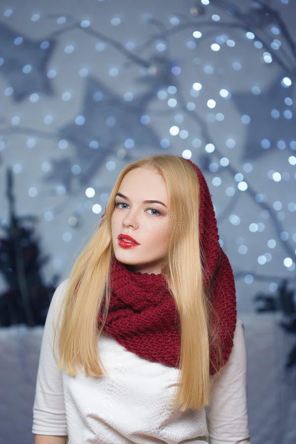Belle fille dans un chapeau rouge à une guirlande de Noël photos libres de droits