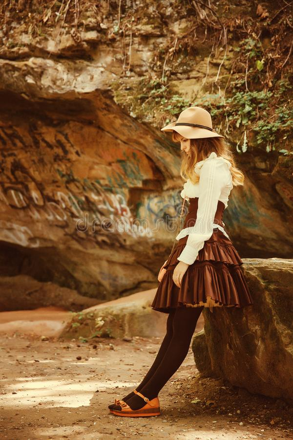 Belle fille dans un chapeau dans une robe de cru Parc d'été en montagnes images libres de droits