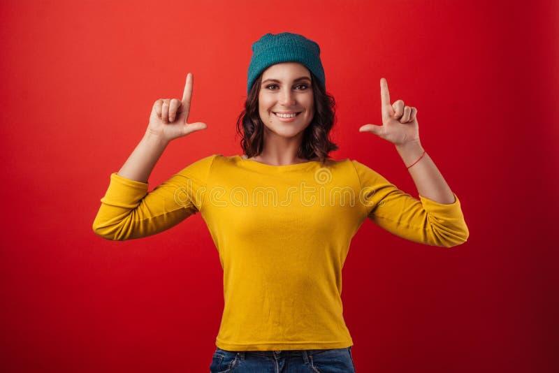 Belle fille dans un chapeau vert et un chandail jaune, souriant photos libres de droits