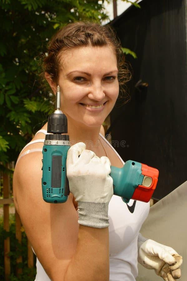 Belle fille dans un T-shirt blanc et des gants tenant un foret, posant dehors photo stock
