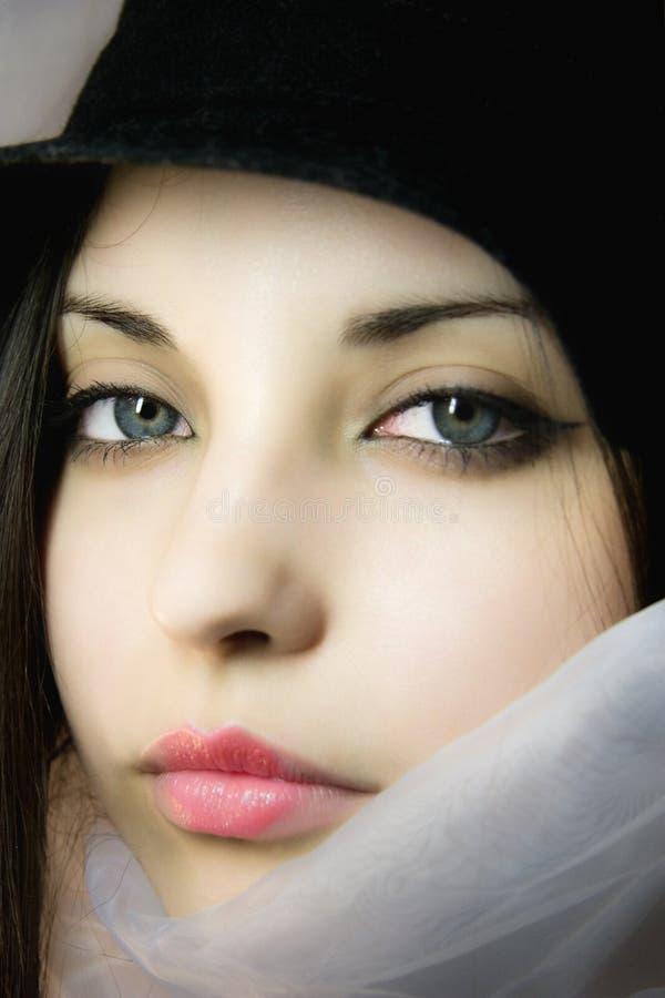 Belle fille dans une écharpe avec des œil bleu image stock
