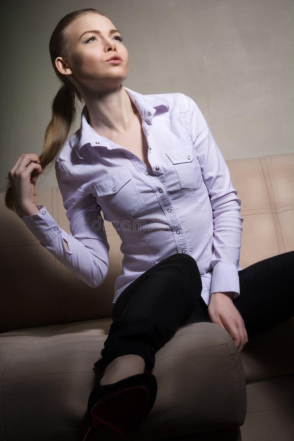 Belle fille dans une chemise blanche se reposant sur le divan photographie stock libre de droits