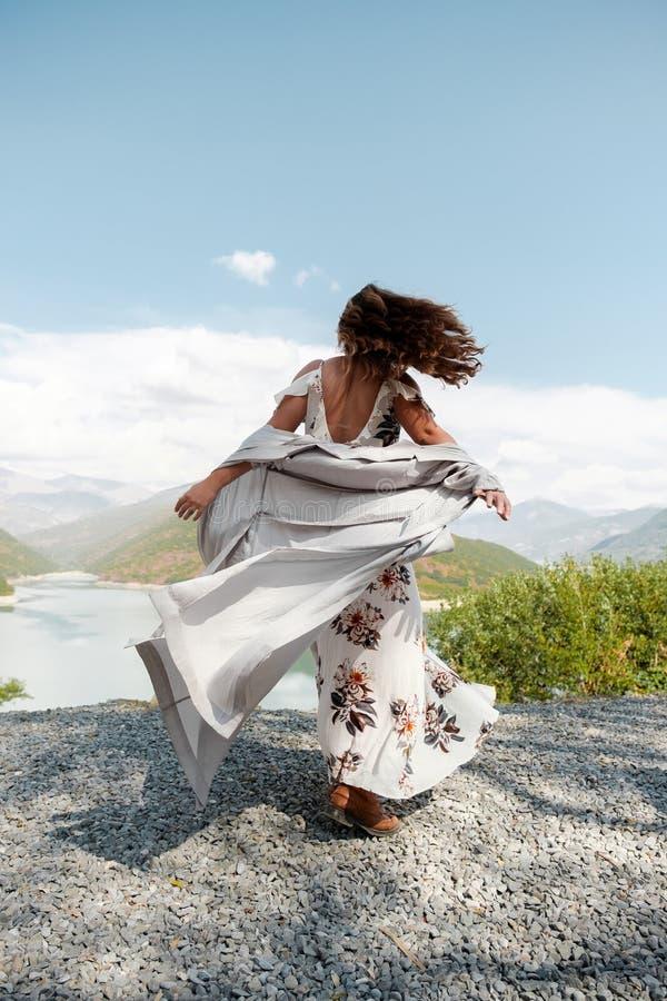 Belle fille dans une longue robe sur un fond d'un lac et des montagnes image stock