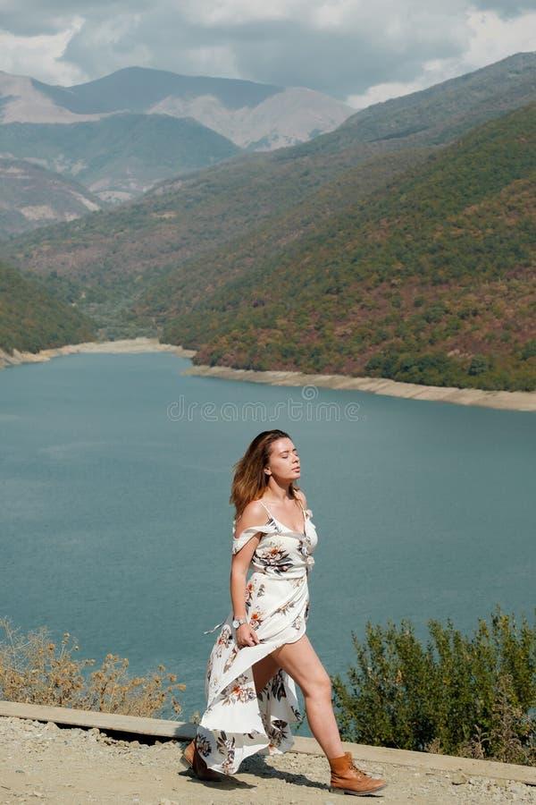 Belle fille dans une longue robe sur un fond d'un lac et des montagnes photo libre de droits