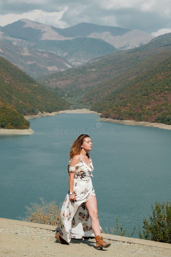 Belle fille dans une longue robe sur un fond d'un lac et des montagnes images libres de droits