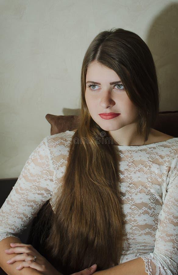 Belle fille dans une robe blanche avec de longs cheveux se reposant sur le divan images stock