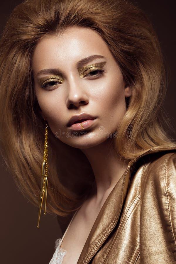 Belle fille dans une robe d'or avec le maquillage créatif et les cheveux La beauté du visage photos libres de droits