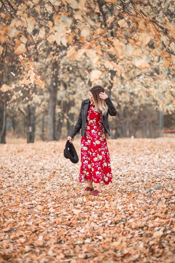 Belle fille dans une robe rouge et des promenades noires de veste en parc d'automne photo libre de droits