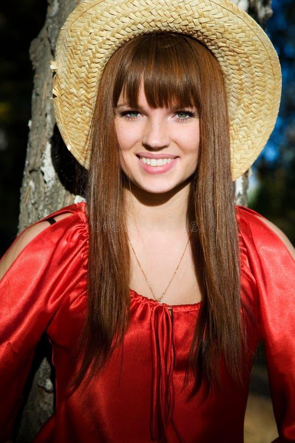Belle fille dans une robe rouge et un chapeau de paille photos libres de droits