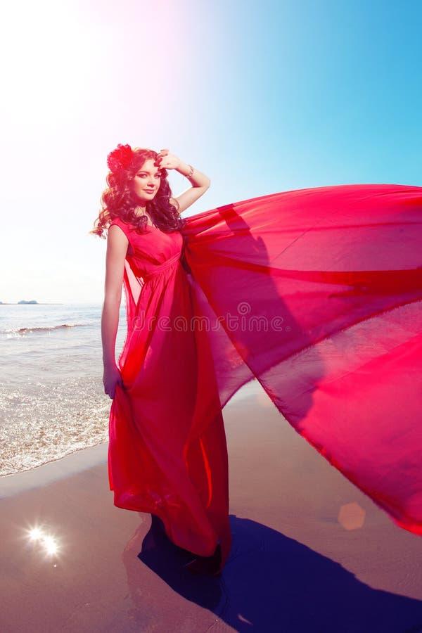Belle fille dans une robe rouge lumineuse par la mer Contre le CCB image stock