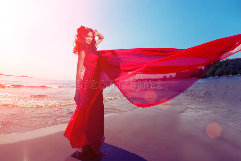Belle fille dans une robe rouge lumineuse par la mer Contre le CCB images stock
