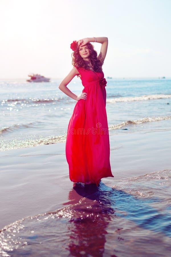 Belle fille dans une robe rouge lumineuse par la mer Contre le CCB photographie stock libre de droits