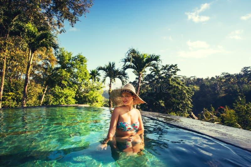 Belle fille de brune appréciant un jour ensoleillé à la piscine d'infini photos stock