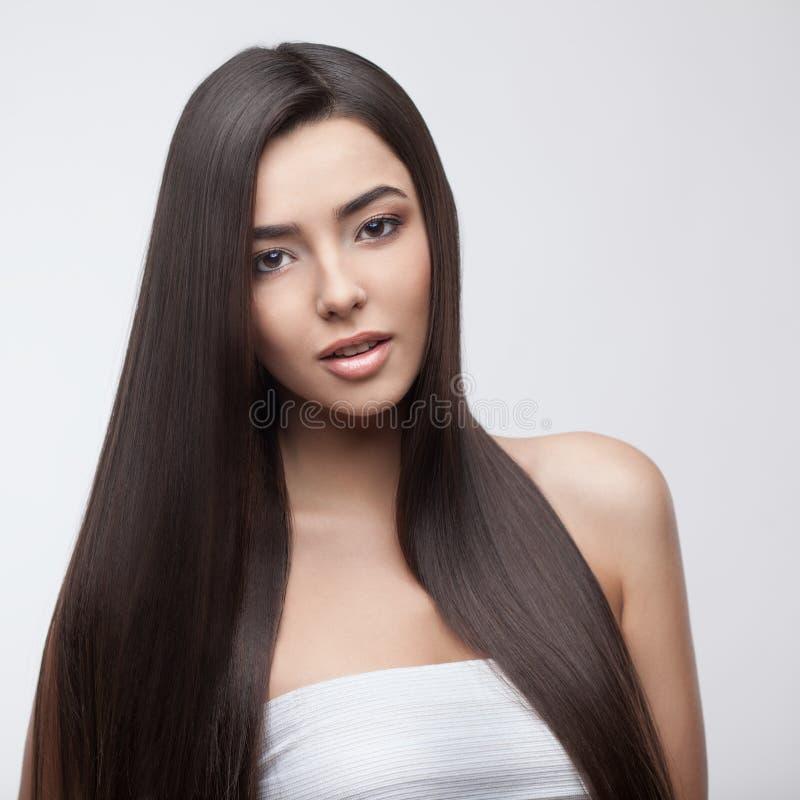 Belle fille de brune avec de longs cheveux sains photographie stock