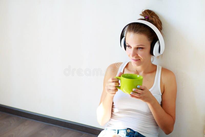 Belle fille de brune avec des écouteurs écoutant la musique et le café potable tout en se reposant sur le plancher dans une salle photographie stock libre de droits