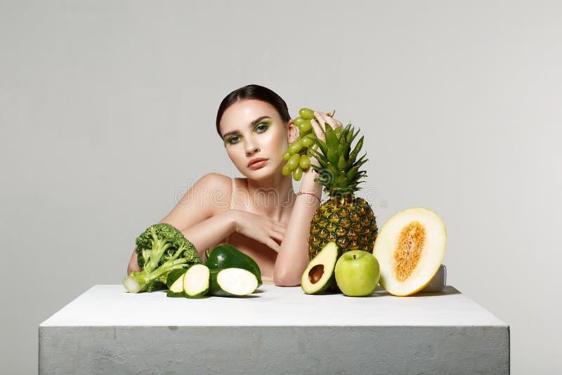 Belle fille de brune avec le maquillage lumineux tenant les raisins verts à disposition, regardant la caméra photo stock