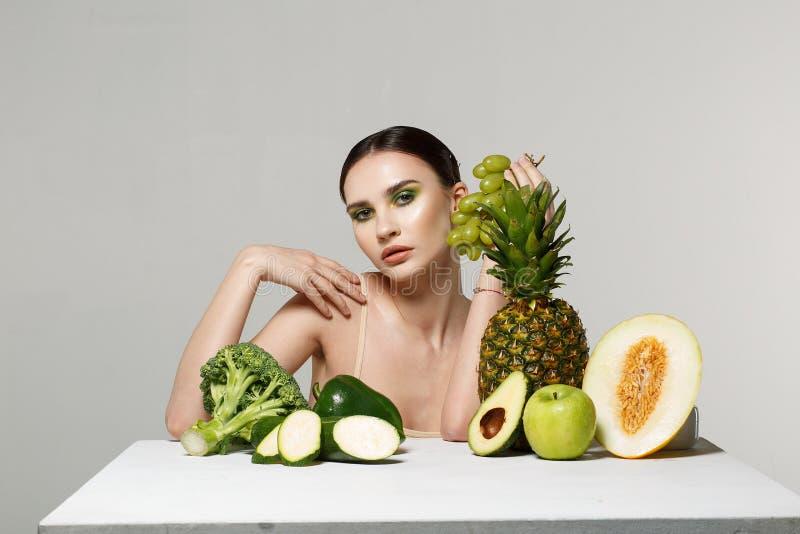 Belle fille de brune avec le maquillage lumineux tenant les raisins verts à disposition, regardant la caméra images stock