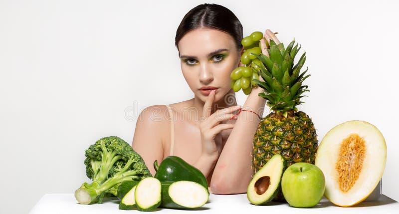 Belle fille de brune avec le maquillage lumineux tenant les raisins verts ? disposition, regardant la cam?ra, fruits et l?gumes s images libres de droits