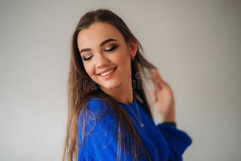 Belle fille de brune avec un beau sourire dans un chemisier bleu posant pour un photographe et lui montrant le maquillage images stock