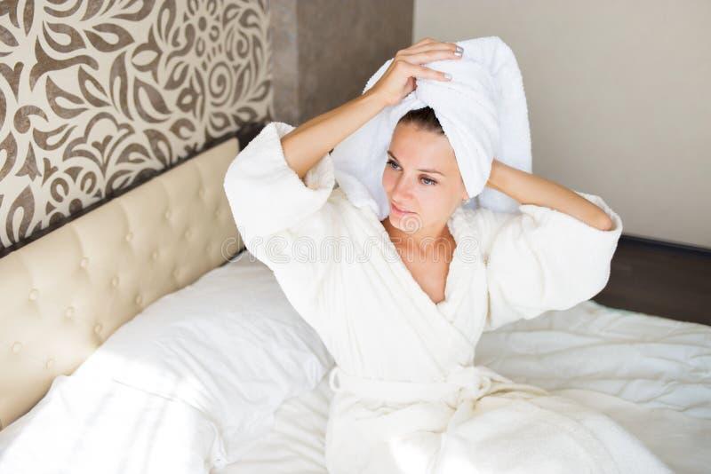 Belle fille de brune avec une serviette sur sa tête dans le lit Elle prenait une douche Concept de matin photographie stock libre de droits