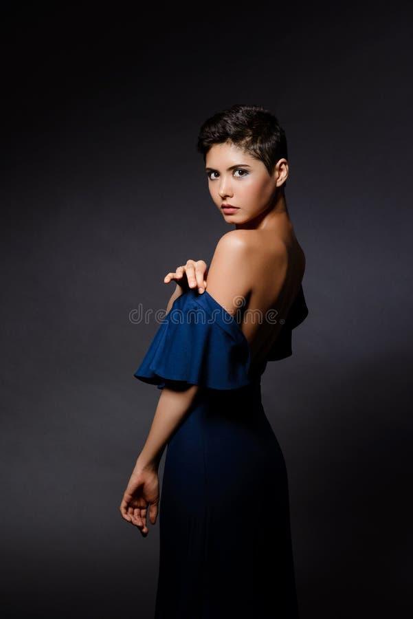 Belle fille de brune dans la robe de soirée posant au-dessus du fond gris images stock
