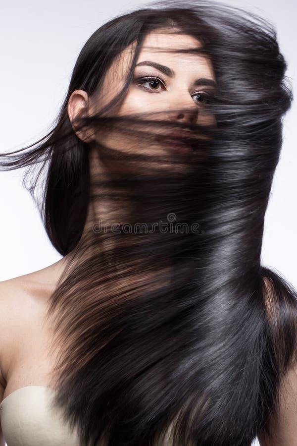 Belle fille de brune dans le mouvement avec des cheveux parfaitement lisses, et maquillage classique Visage de beauté images stock