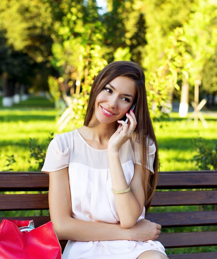 Belle fille de brune parlant au téléphone dans un banc de séance de parc dans la robe, détente de femme d'affaires de jour d'été image libre de droits