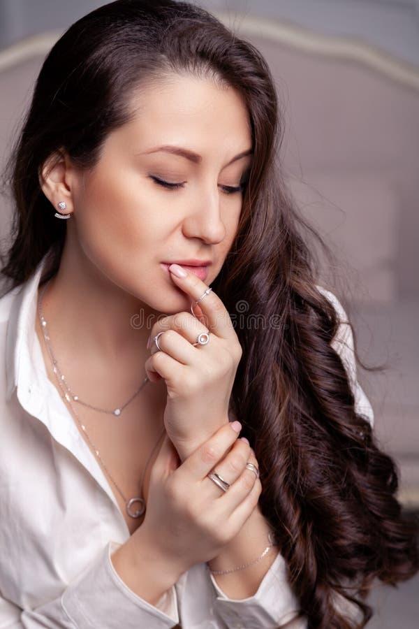 Belle fille de brune de plan rapproché avec de longs cheveux en boucles d'oreille, anneaux, bracelet et collier argentés de bij images stock