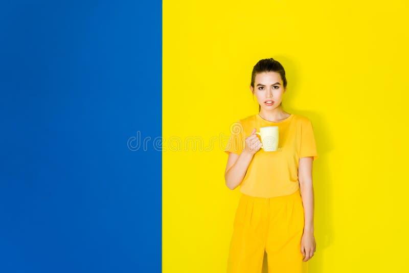 Belle fille de brune tenant la tasse jaune sur le bleu photos libres de droits