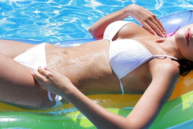 Belle fille de corps sur un matelas dans la piscine images stock