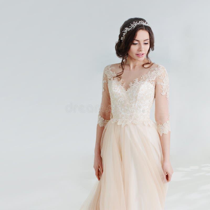 Belle fille de danse dans une robe de mariage Jeune mariée dans la robe luxueuse sur un fond blanc images libres de droits