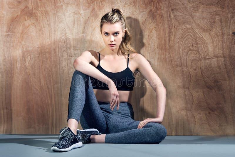 Belle fille de forme physique détendant après séance d'entraînement dans le gymnase et s'asseyant près du mur photo libre de droits