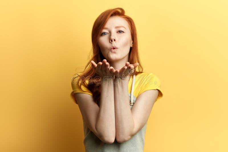 Belle fille de gingembre dans l'équipement occasionnel envoyant le baiser de soufflement photographie stock