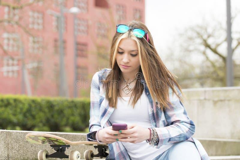 Belle fille de hippie de portrait avec le skatebord et le téléphone intelligent photographie stock libre de droits