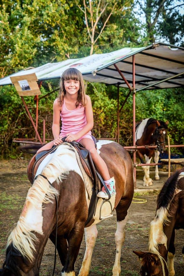 Belle fille de huit ans sur le cheval photo libre de droits