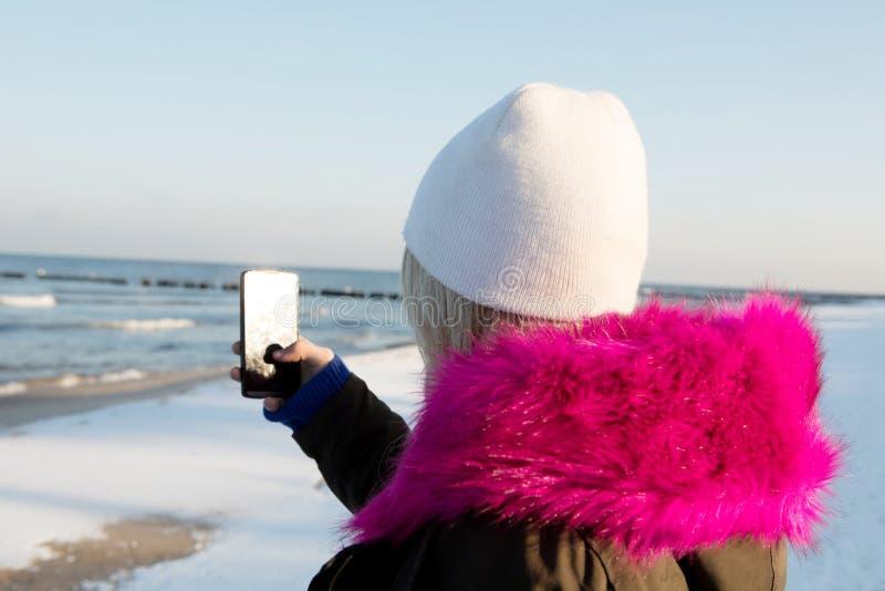 Belle fille de jeune adolescent ayant l'amusement et faisant le selfie photographie stock