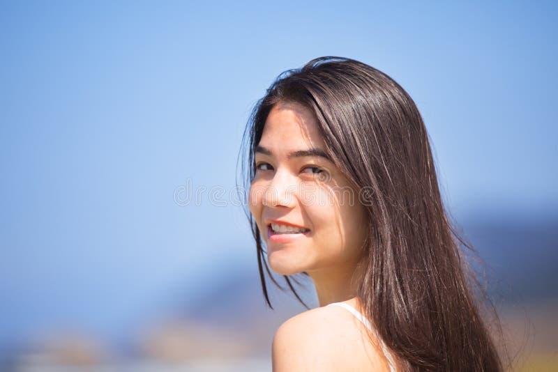 Belle fille de l'adolescence à la plage le jour ensoleillé, souriant photographie stock