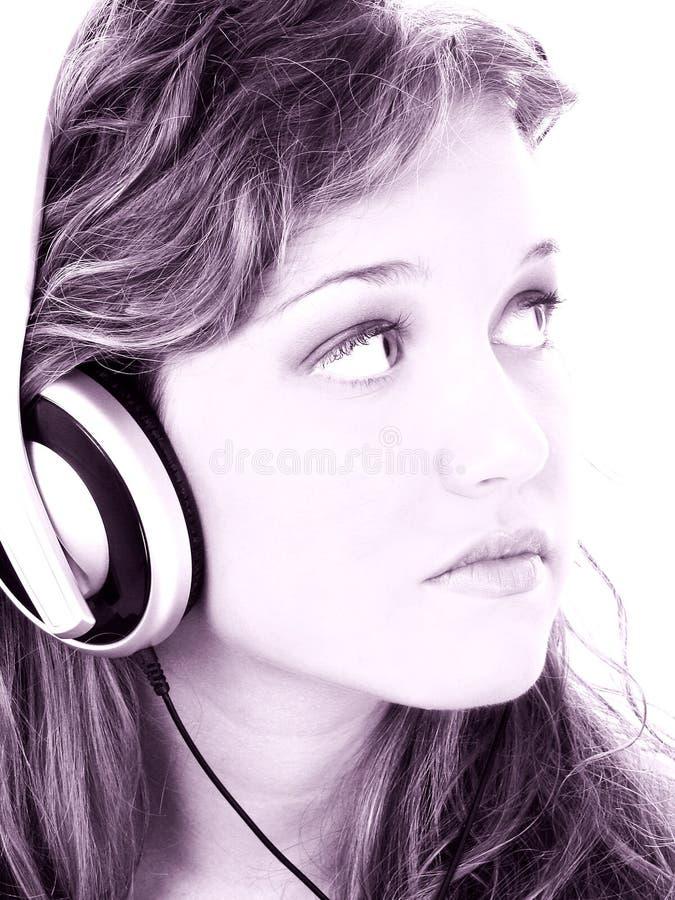 Belle fille de l'adolescence écoutant des écouteurs dans des sons de raisin images stock
