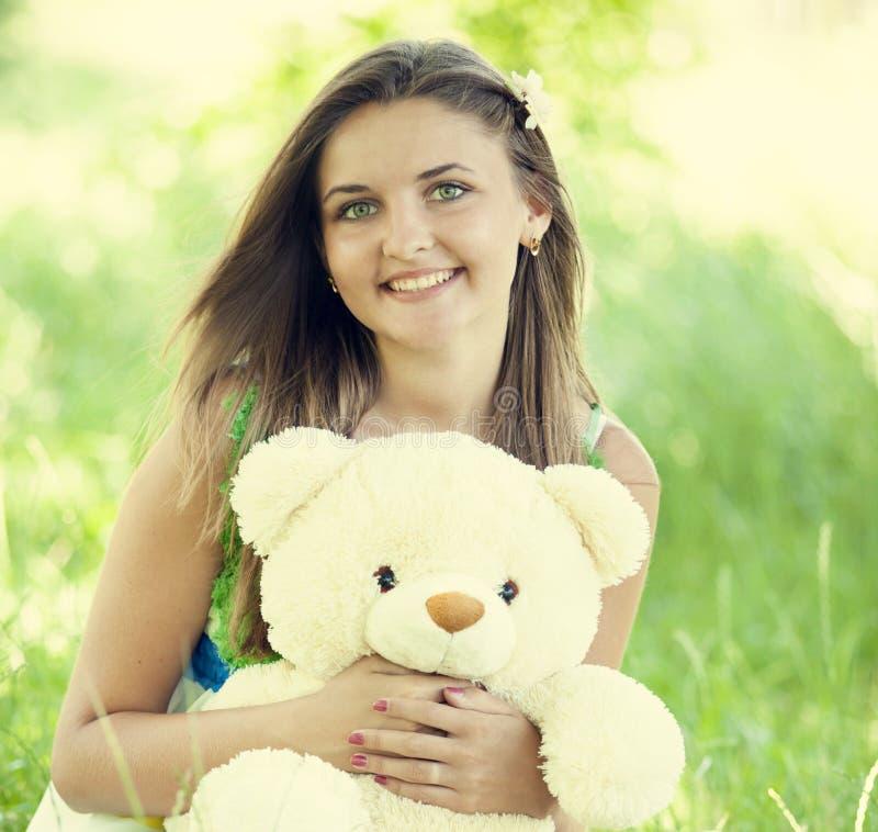 Belle fille de l'adolescence avec l'ours de nounours en stationnement à l'herbe verte. photographie stock