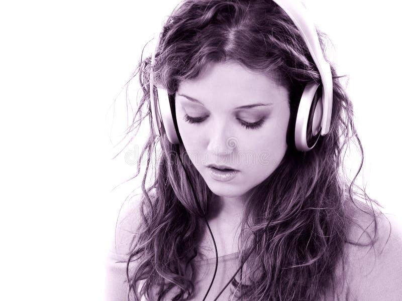 Belle fille de l'adolescence avec les écouteurs et l'ordinateur portatif photographie stock libre de droits
