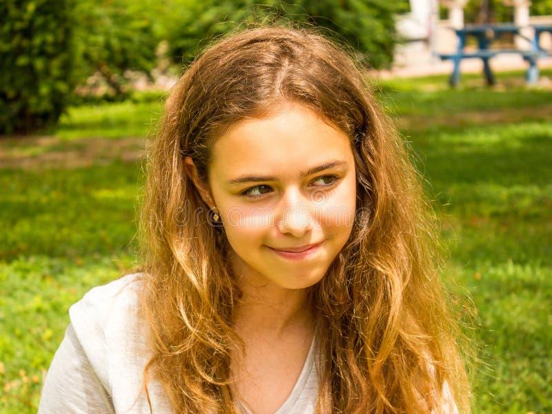 Belle fille de l'adolescence avec de longs cheveux souriant en parc sur l'herbe verte photos stock