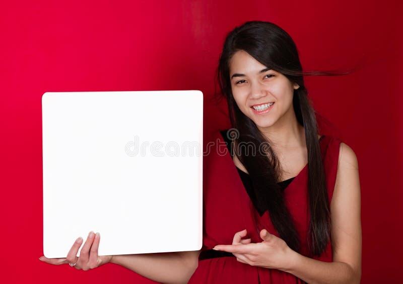 Belle fille de l'adolescence biracial retardant le signe blanc carré, point photographie stock