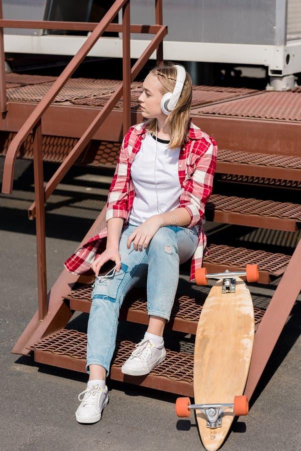 belle fille de l'adolescence dans la chemise de plaid rouge et des écouteurs se reposant sur des escaliers photographie stock libre de droits