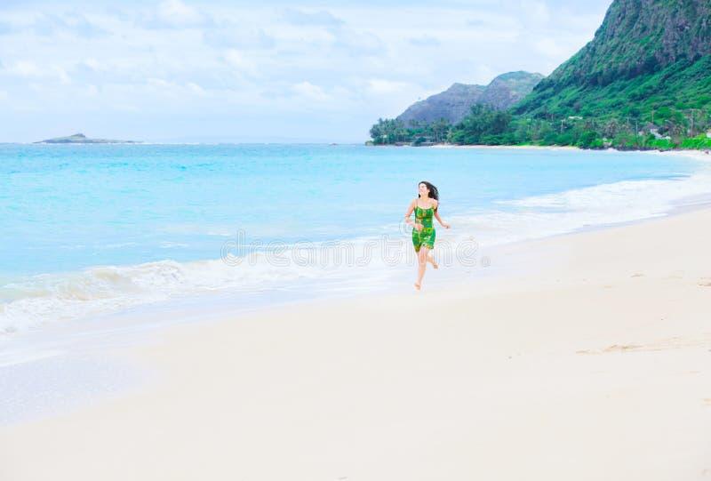 Belle fille de l'adolescence dans la robe verte fonctionnant sur la plage hawaïenne photo libre de droits