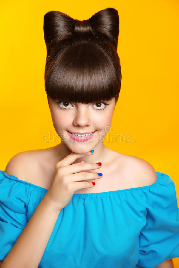 Belle fille de l'adolescence de sourire avec la coiffure, le maquillage et le colou d'arc photo libre de droits
