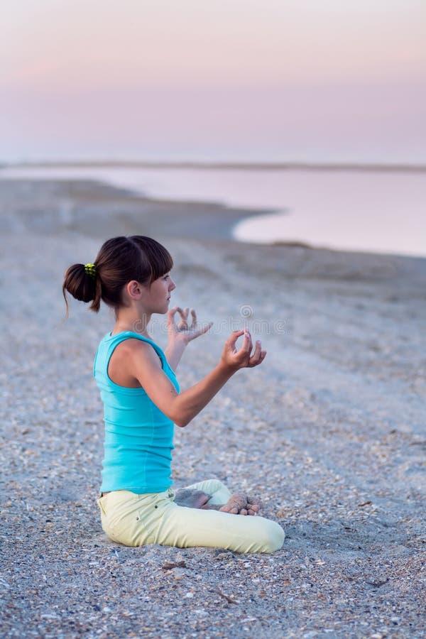 Belle fille de l'adolescence faisant la pose de lotus d'exercice de yoga sur le fond de la mer au coucher du soleil, photo stock