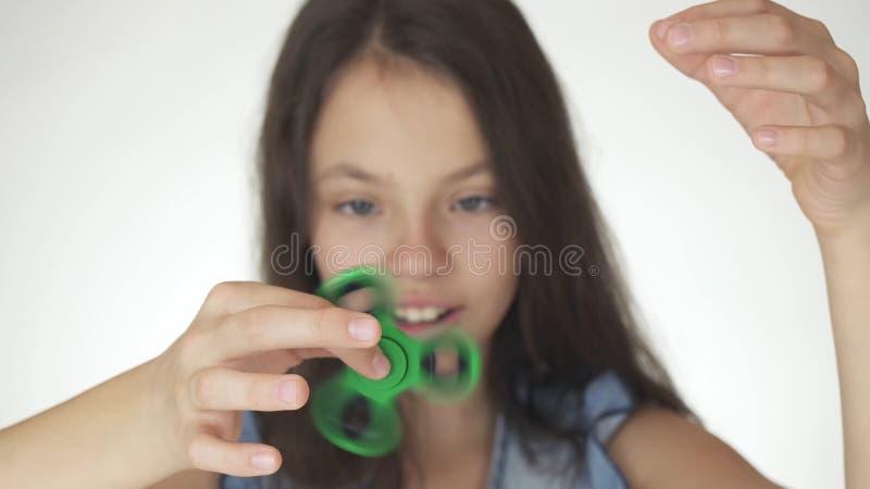 Belle fille de l'adolescence gaie jouant avec le fileur vert de personne remuante sur le fond blanc photo stock