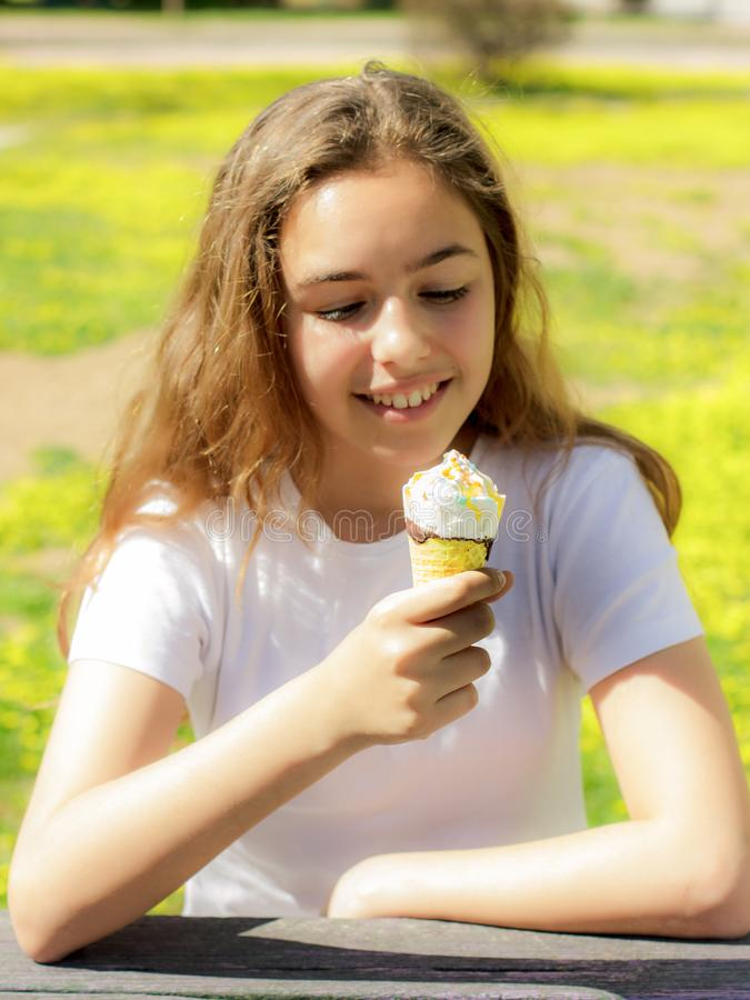 Belle fille de l'adolescence mangeant la cr?me glac?e dans un c?ne de gaufre en ?t? Foyer s?lectif photographie stock libre de droits