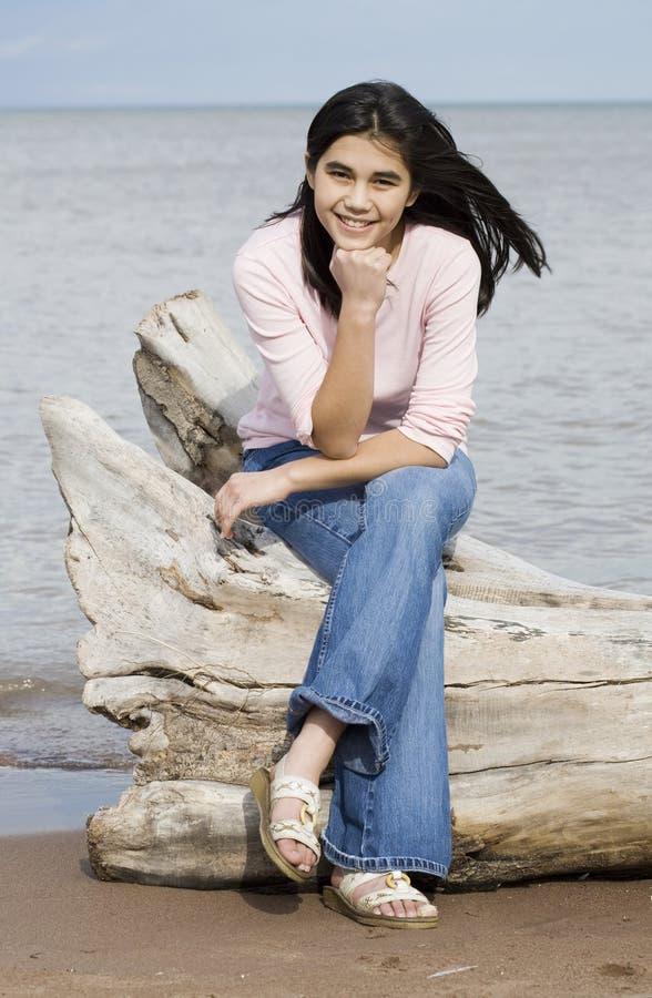 Belle fille de l'adolescence s'asseyant sur le logarithme naturel photographie stock libre de droits