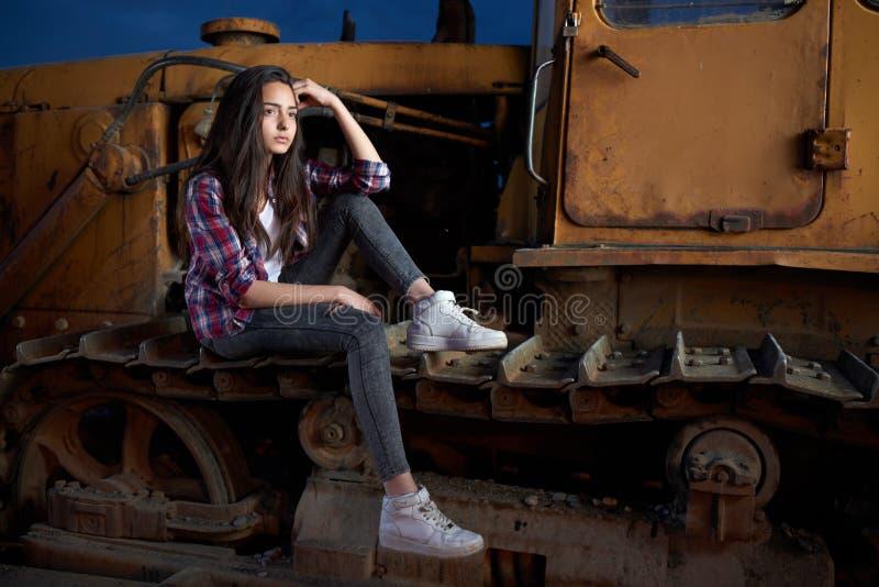 Belle fille de l'adolescence s'asseyant sur un vieux tracteur photo libre de droits